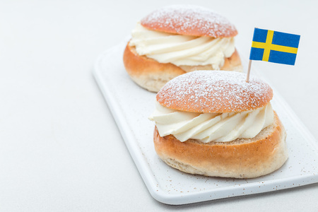 Traditional swedish dessert Semla, also called Shrove bun, with almond paste and whipped cream filling, horizontal, copy space