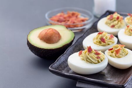 Deviled eggs stuffed with avocado, egg yolk and mayonnaise filling, garnished with bacon, horizontal, copy space