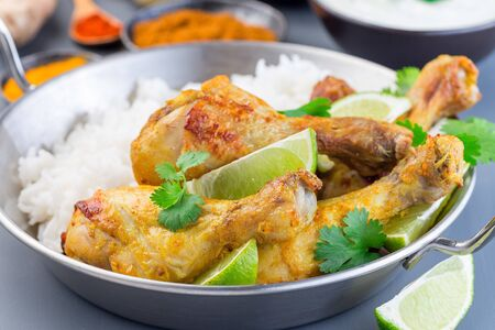 Indian chicken tandoori, marinated in greek yogurt  and spices, served with lime wedges, cilantro and basmati rice,  horizontal Stock Photo - 126330540