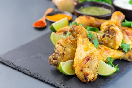 Indian chicken tandoori, marinated in greek yogurt  and spices, served with lime wedges and cilantro on a slate plate, horizontal, copy space