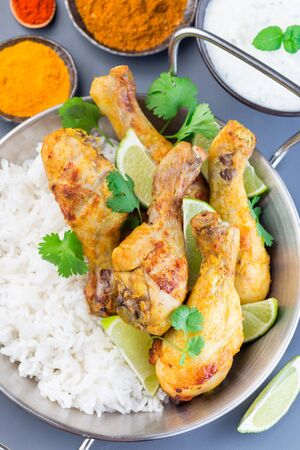 Indian chicken tandoori, marinated in greek yogurt  and spices, served with lime wedges, cilantro and basmati rice, vertical,   top view