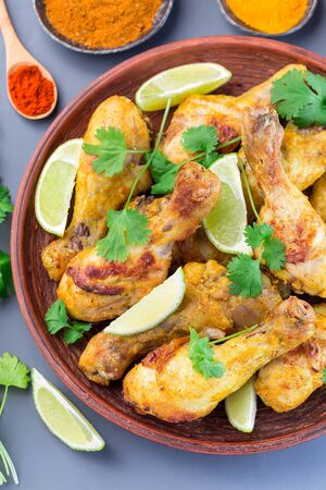 Indian chicken tandoori, marinated in greek yogurt  and spices, served with lime wedges and cilantro, vertical, top view Stock Photo - 126327163
