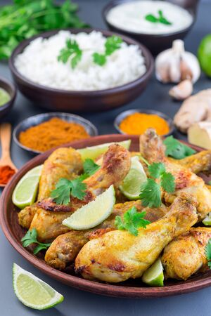 Indian chicken tandoori, marinated in greek yogurt  and spices, served with lime wedges and cilantro, vertical Stock Photo - 126331468