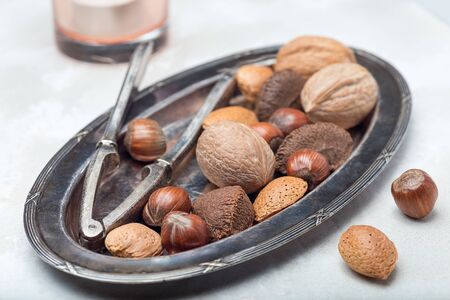Different kinds of nuts in shell, hazelnut, walnut, almond and brazil nuts on the plate with nut cracker, horizontal