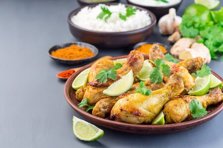 Indian chicken tandoori, marinated in greek yogurt  and spices, served with lime wedges and cilantro, horizontal,  copy space Stock Photo - 126328241