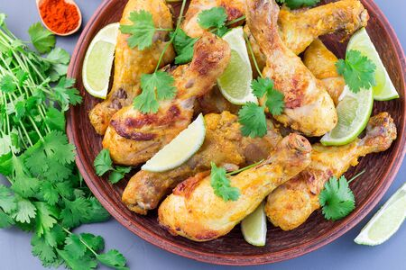 Indian chicken tandoori, marinated in greek yogurt and spices, served with lime wedges and cilantro, horizontal, top view