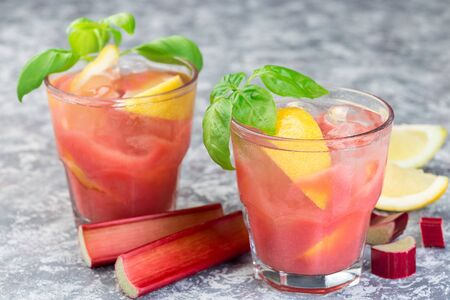Refreshing lemonade with rhubarb, lemon, sparkling water and basil in a glass, horizontal Stock Photo