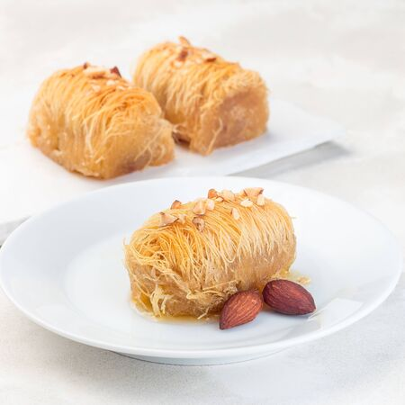 Greek pastry Kataifi with shredded filo dough stuffed with almond nuts, in honey syrup, on a white plate, square format