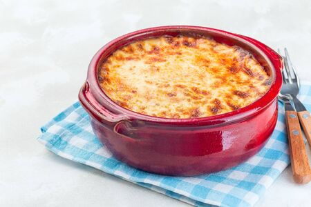 Greek dish moussaka made in a traditional ceramic pot, horizontal, copy space
