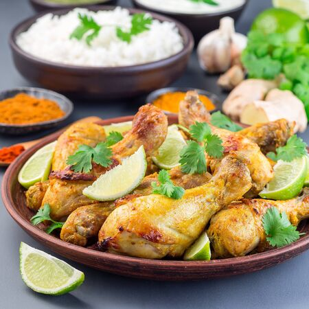 Indian chicken tandoori, marinated in greek yogurt  and spices, served with lime wedges and cilantro,  square format Stock Photo