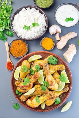 Indian chicken tandoori, marinated in greek yogurt  and spices, served with lime wedges and cilantro, vertical,  top view Stock Photo
