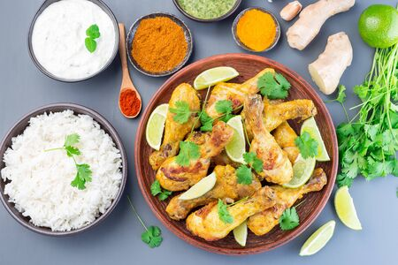Indian chicken tandoori, marinated in greek yogurt  and spices, served with lime wedges and cilantro, horizontal,  top view Stock Photo