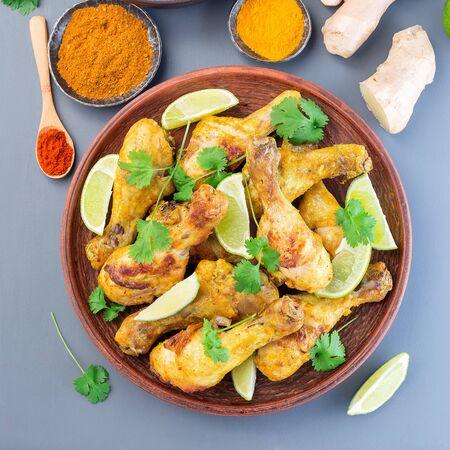 Poulet tandoori indien, mariné dans du yaourt grec et des épices, servi avec des quartiers de citron vert et de la coriandre, vue de dessus, format carré Banque d'images