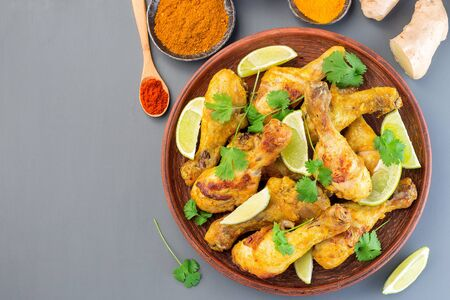Indian chicken tandoori, marinated in greek yogurt  and spices, served with lime wedges and cilantro, horizontal, top view, copy space