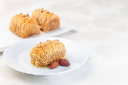 Greek pastry Kataifi with shredded filo dough stuffed with almond nuts, in honey syrup, on a white plate, horizontal, copy space