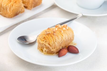 Greek pastry Kataifi with shredded filo dough stuffed with almond nuts, in honey syrup, on white plate, horizontal