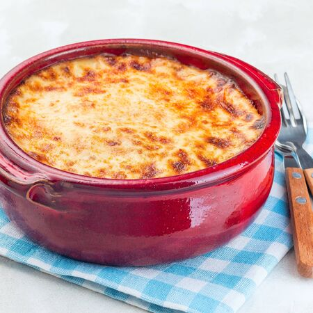 Greek dish moussaka made in a traditional ceramic pot, square format