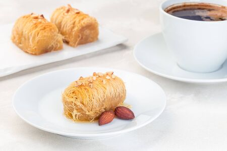 Greek pastry Kataifi with shredded filo dough stuffed with almond nuts, in honey syrup, on a white plate, served with a cup of coffee, horizontal