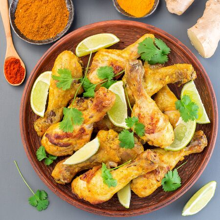 Indian chicken tandoori, marinated in greek yogurt  and spices, served with lime wedges and cilantro, top view,  square format, closeup