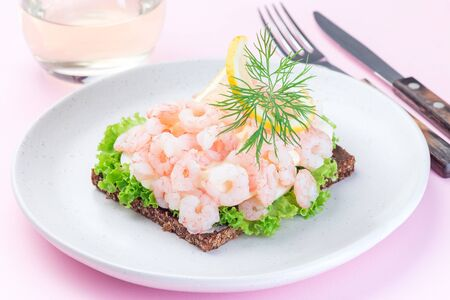 Traditional savory swedish sandwich with dark bread, lettuce, eggs, mayonnaise, shrimps, dill and lemon, on a pink background, horizontal