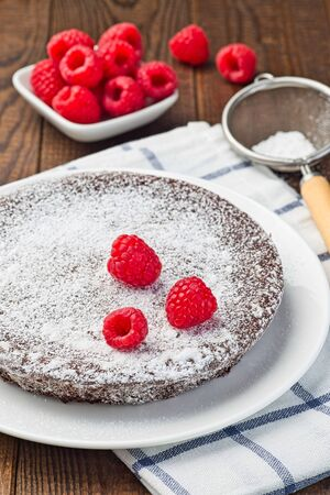 Chocolate sticky brownie cake, swedish dessert Kladdkaka, on the plate, garnished with icing sugar and raspberry, vertical