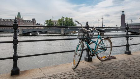 Blue bicycle with shopping basket stand on the bank of the river in Stockholm, Sweden Reklamní fotografie