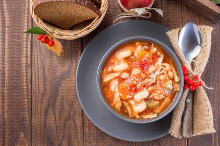 Soup with turkey, pasta, carrot, celery, tomato and cannellini beans, garnished with parmesan cheese, on the table with autumn decoration, reflecting the US Thanksgiving harvest feast, horizontal, top