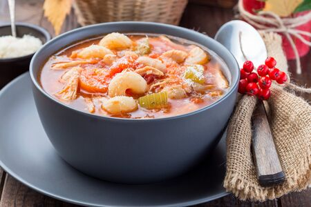 Soup with turkey, pasta, carrot, celery, tomato and cannellini beans, garnished with parmesan cheese, on the table with autumn decoration, reflecting the US Thanksgiving harvest feast, horizontal,  cl