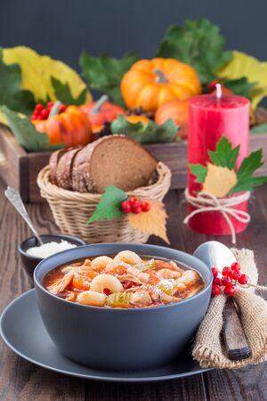 Soup with turkey, pasta, carrot, celery, tomato and cannellini beans on the table with autumn decoration, reflecting the US Thanksgiving harvest feast,  vertical