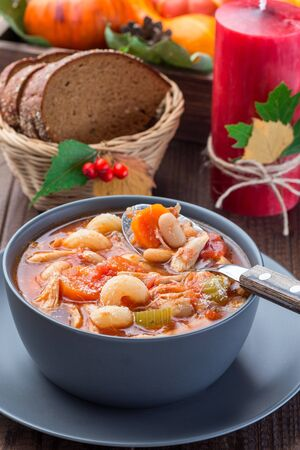 Soup with turkey, pasta, carrot, celery, tomato and cannellini beans, garnished with parmesan cheese, on the table with autumn decoration, reflecting the US Thanksgiving harvest feast, vertical,  clos