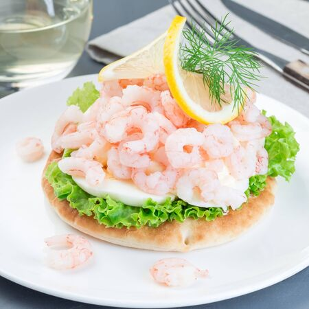 Traditional savory swedish sandwich with soft white bread vetekaka, lettuce, eggs, mayonnaise, shrimps, dill and lemon, square format