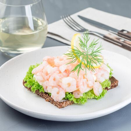 Traditional savory swedish sandwich with a dark bread, lettuce, eggs, mayonnaise, shrimps, dill and lemon, square