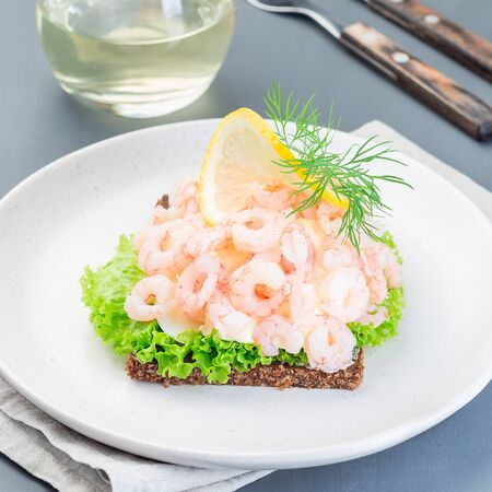 Traditional savory swedish sandwich with a dark bread, lettuce, eggs, mayonnaise, shrimps, dill and lemon, square format