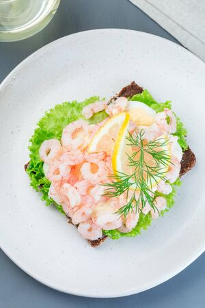 Traditional savory swedish sandwich with a dark bread, lettuce, eggs, mayonnaise, shrimps, dill and lemon, vertical, top view Stok Fotoğraf