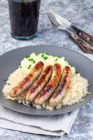 Roasted nuremberg sausages served with sour cabbage and mashed potatoes, vertical
