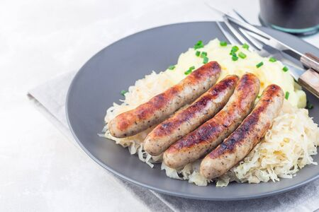 Roasted nuremberg sausages served with sour cabbage and mashed potatoes, on a gray plate, horizontal, copy space