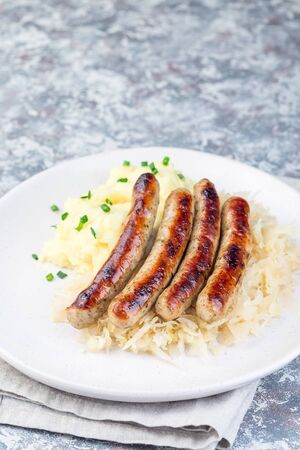 Roasted nuremberg sausages served with sour cabbage and mashed potatoes, on a white plate, vertical, copy space