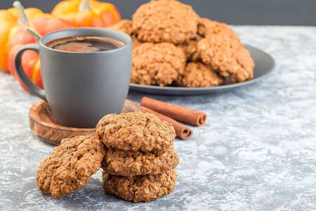 Spicy pumpkin and oatmeal cookies on the table and on a plate, with a cup of coffee, horizontal, copy space
