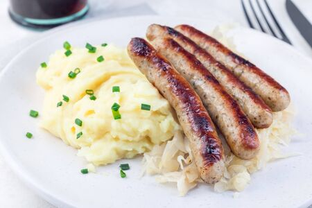 Roasted nuremberg sausages served with sour cabbage and mashed potatoes, on a white plate, horizontal