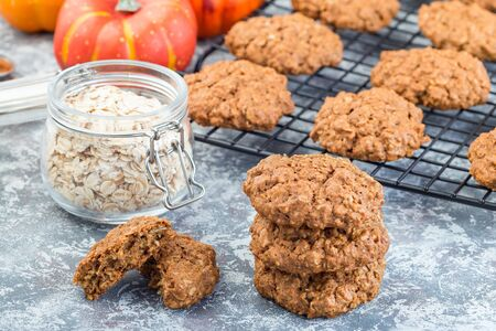 Spicy pumpkin and oatmeal cookies on the table and on a cooling rack, horizontal