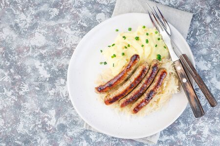 Roasted nuremberg sausages served with sour cabbage and mashed potatoes, on a white plate, horizontal, top view, copy space