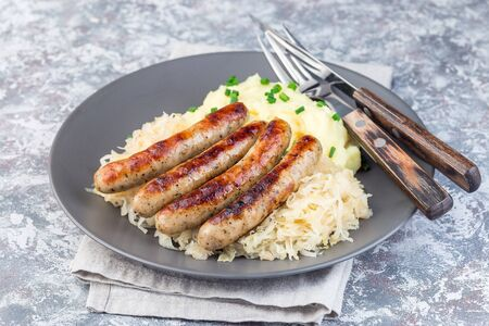 Roasted nuremberg sausages served with sour cabbage and mashed potatoes, on a gray plate, horizontal