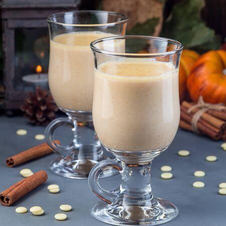 Heiße weiße Schokolade mit Kürbis und Gewürzen, Herbstdekorationen im Hintergrund, quadratisch