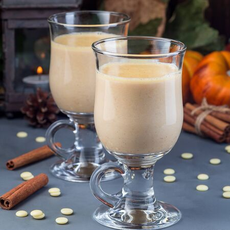 Hot white chocolate with pumpkin and spices, autumn decorations on background, square