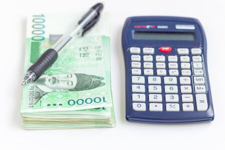 South Korean won currency in 10 000 won value with calculator and pen, save your money  concept