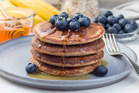 Healthy oatmeal banana pancakes garnished with blueberry and honey, on a gray plate, horizontal Stockfoto