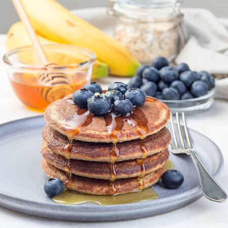 Healthy oatmeal banana pancakes garnished with blueberry and honey, on a gray plate, square format