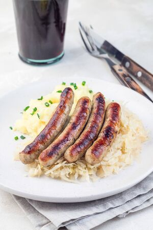 Roasted nuremberg sausages served with sour cabbage and mashed potatoes, on a white plate, vertical