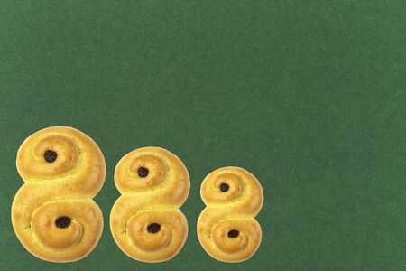Traditional Swedish and scandinavian Christmas saffron buns Lussekatter on a green background, horizontal, copy space