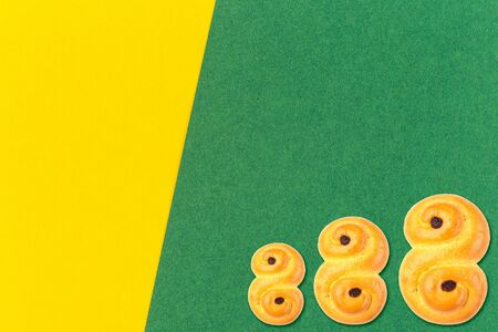 Traditional Swedish and scandinavian Christmas saffron buns Lussekatter on a green and yellow background, horizontal, copy space